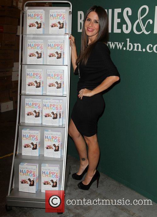 Signs copies of her book 'Happy Chaos: From...