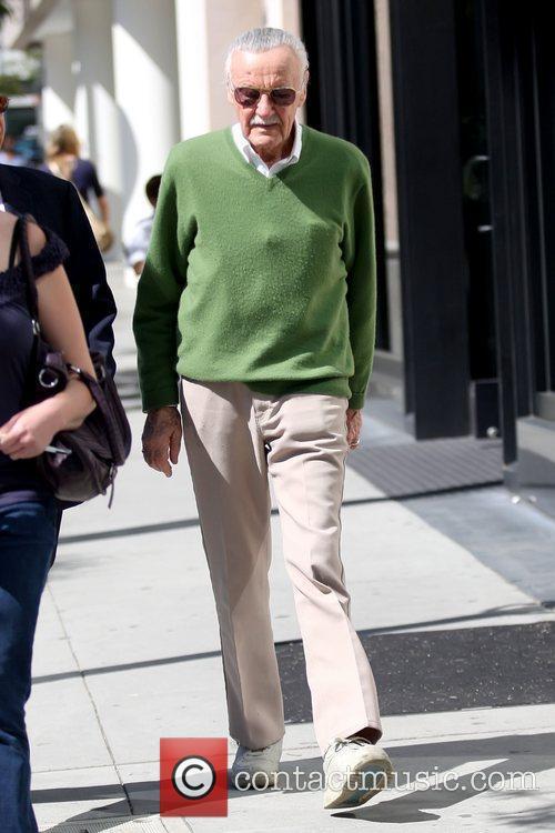 Stan Lee wearing a green sweater as he...