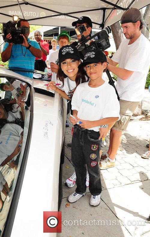 Eva Longoria participates by autographing a car participates...