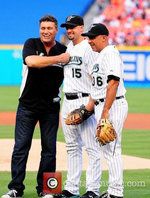 Steven Bauer (L) throw the first pitch during...