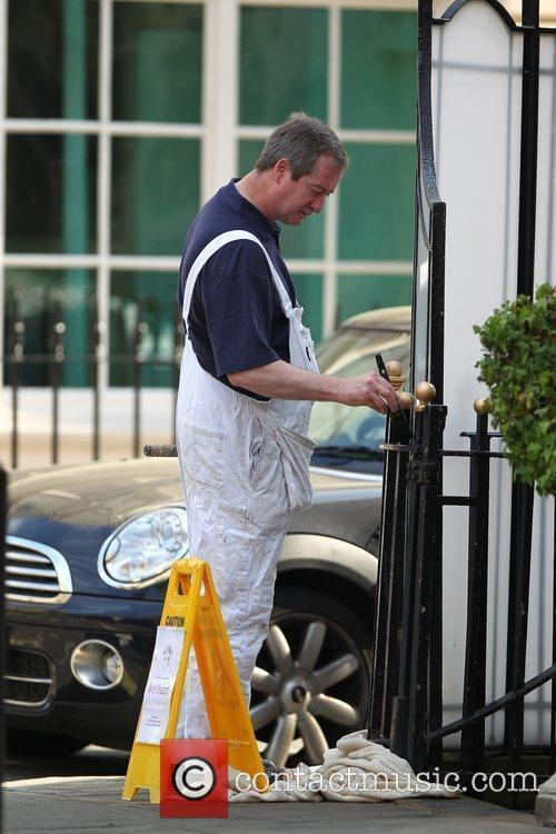 A decorator paints the railings outside The Goring...
