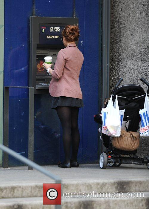 Tina O'Brien with daughter Scarlett taking out money...