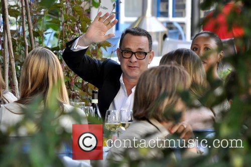Tom Hanks eating with friends at an outside...