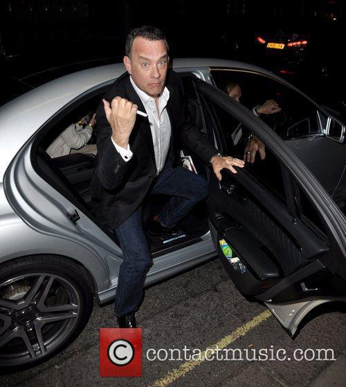 Tom Hanks returning to his hotel holding a...