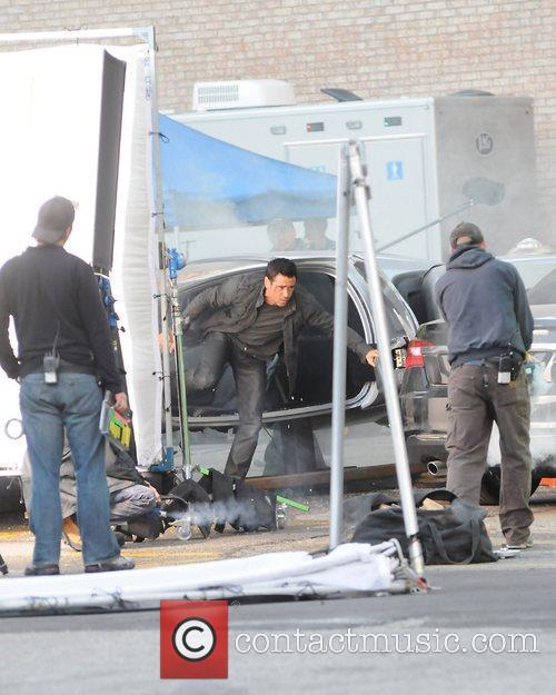 Colin Farrell in a futuristic hovering car on...
