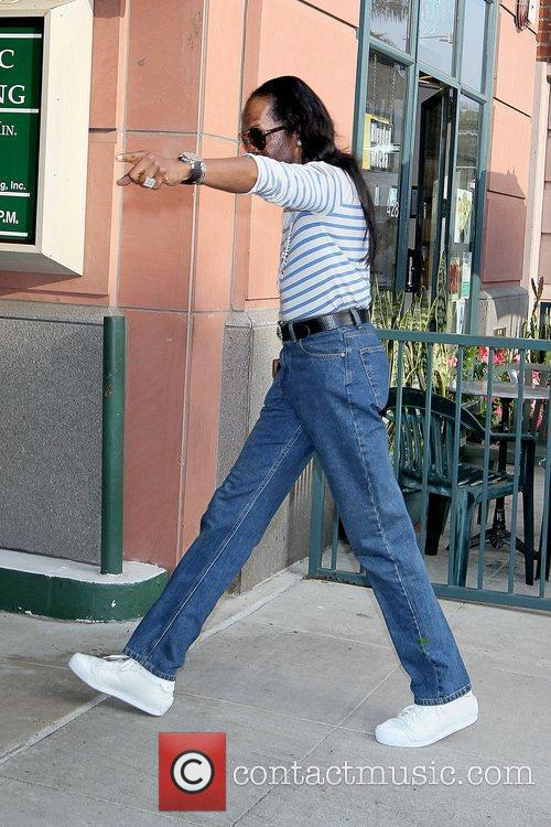 Wearing a striped shirt tucked into his jeans,...