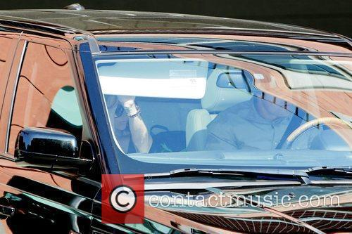 Victoria Beckham driven by her bodyguard in a...