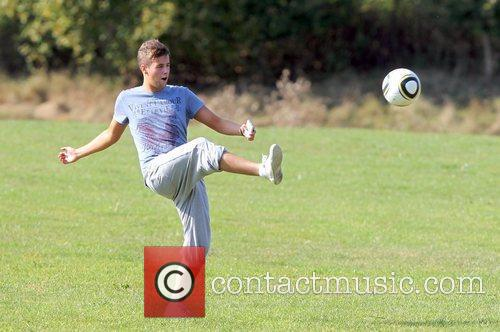 'X Factor' finalist Andrew Merry plays football outside...