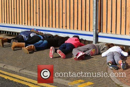 Fans lying on the ground to catch a...