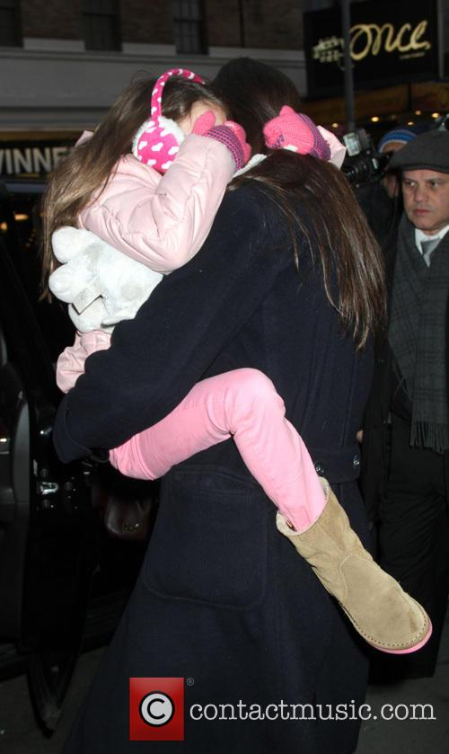 Katie Holmes carries her daughter Suri Cruise in...