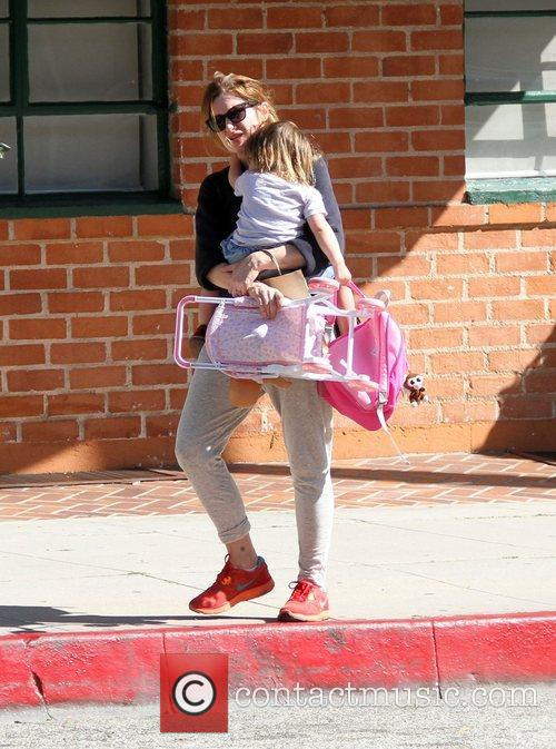 Leaves a medical office with her daughter in...