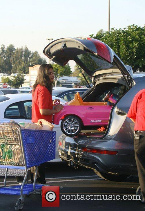 A Toys R US employee helps Jessica Alba...