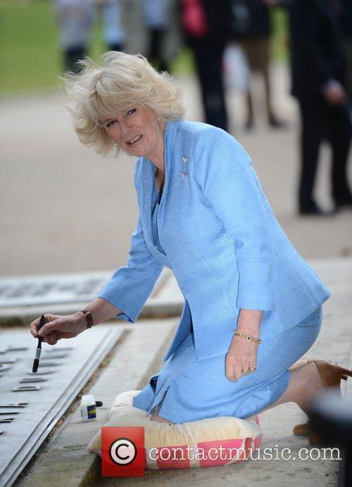 Camilla Duchess of Cornwall marks a statue with...