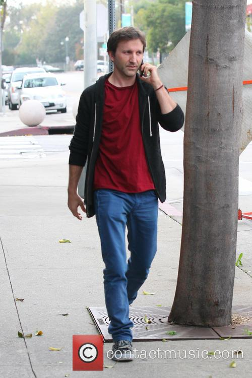 Breckin Meyer talks on his mobile phone while...