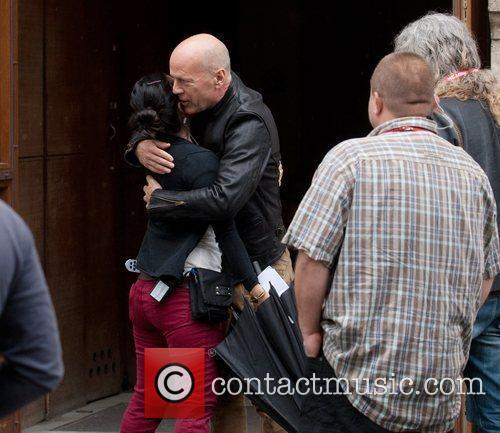 Bruce Willis hugs a friend as he arrives...