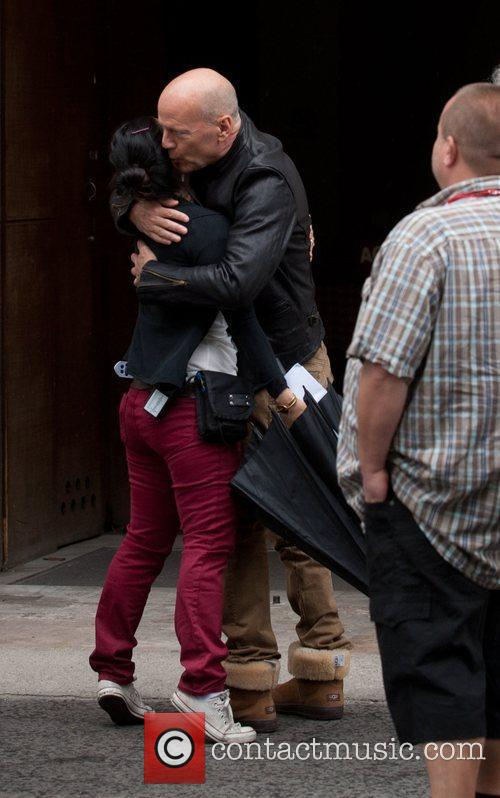 Bruce Willis hugs and kisses a friend as...