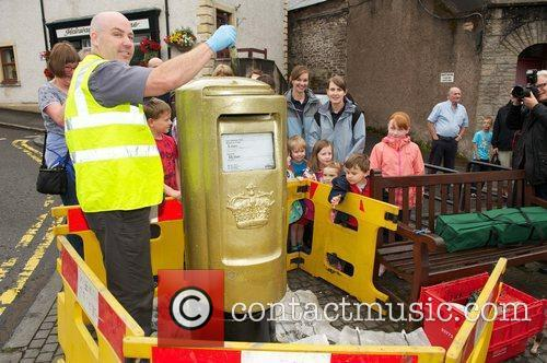 Owen Smith painting the postbox A postbox is...