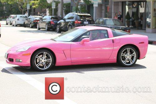 Los Angeles icon, Angelyne drives down the street...
