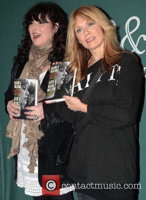 Ann and Nancy Wilson sign copies of their...