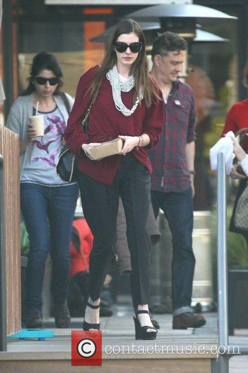 Anne Hathaway departs a restaurant with carry out...