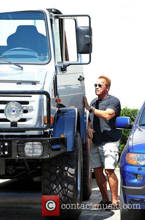 Arnold Schwarzenegger drives an oversized Mercedes-Benz truck to...