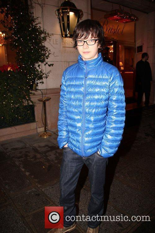 Asa Butterfield in a blue quilted jacket outside...