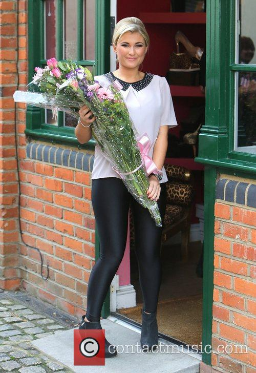 Holds a bunch of flowers outside her shop...