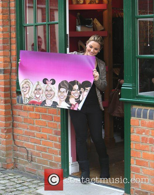 Sam Faiers holds up a caricature poster of...