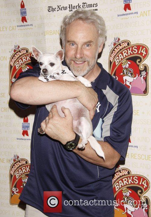 John Dossett holds Chachi, a dog up for...