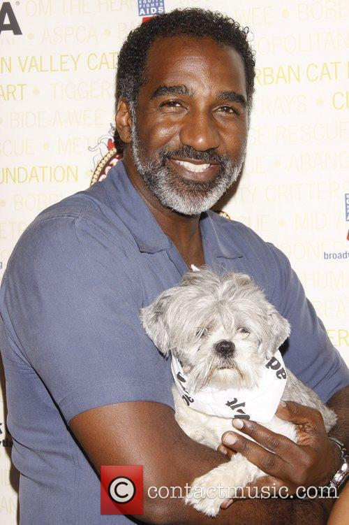 Norm Lewis holds Pepsi, a dog up for...