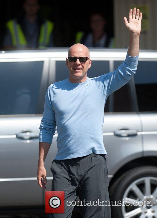 Bruce Willis waves to fans at Budapest Airport...