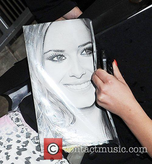 Cheryl Cole holding a picture of herself leaving...