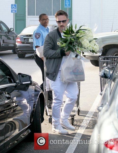 David Arquette carrying flowers after getting supplies for...
