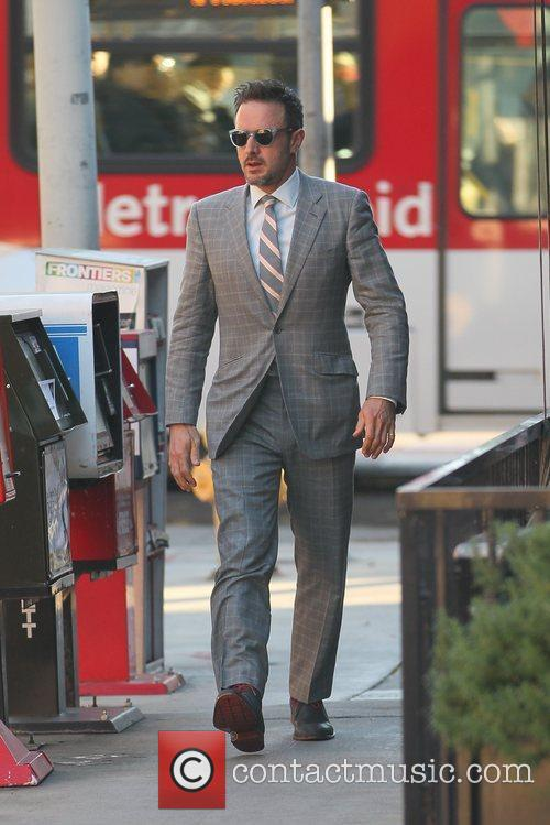 Departs a business meeting wearing a suit