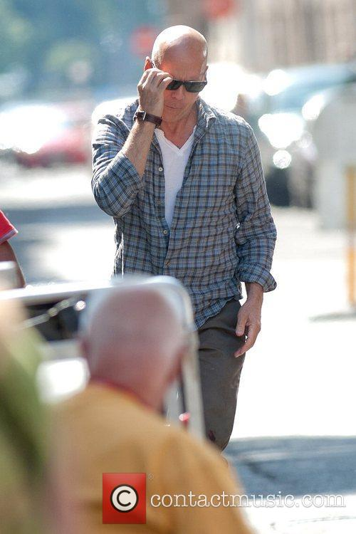 Bruce Willis puts on his sunglasses as he...