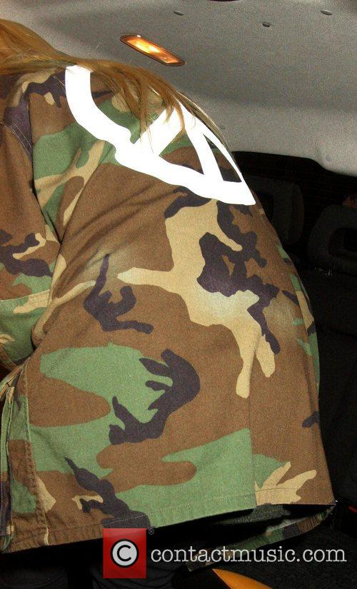 Elle Fanning's camouflage jacket, which has a peace...