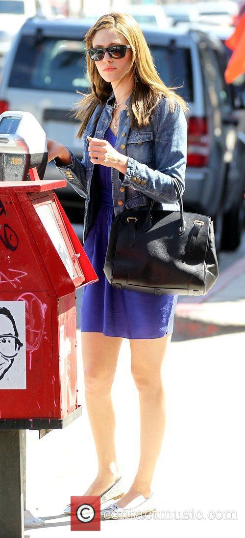 Emmy Rossum feeds a parking meter while out...
