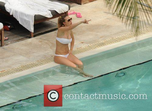 Ilary Blasi relaxes by the pool on holiday...