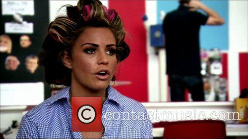 Katie Price with her hair in roller, is...