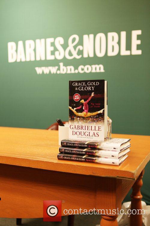 U.S. Olympic gymnast Gabrielle Douglas signs copies of...