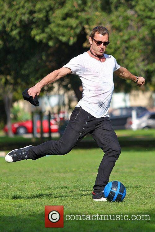 Gavin Rossdale kicking a soccer ball at a...