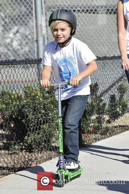 Kingston Rossdale riding his scooter at a park...