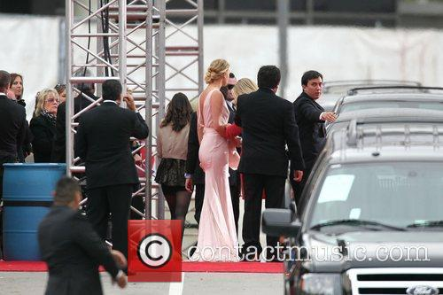 charlize theron readjusts her dress after getting 3686354