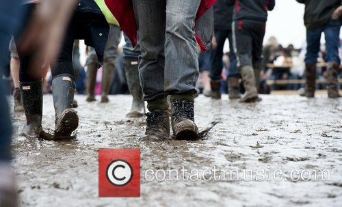 Revelers wearing wellingtons and boots trudge through the...