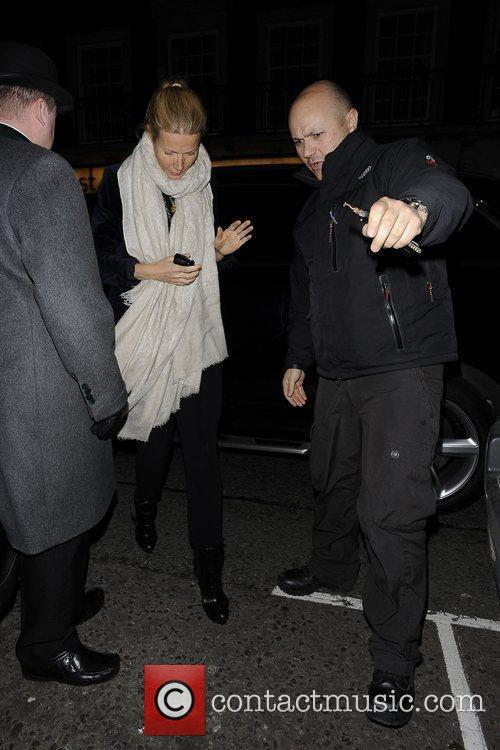 Hides her face from cameras while heading to...