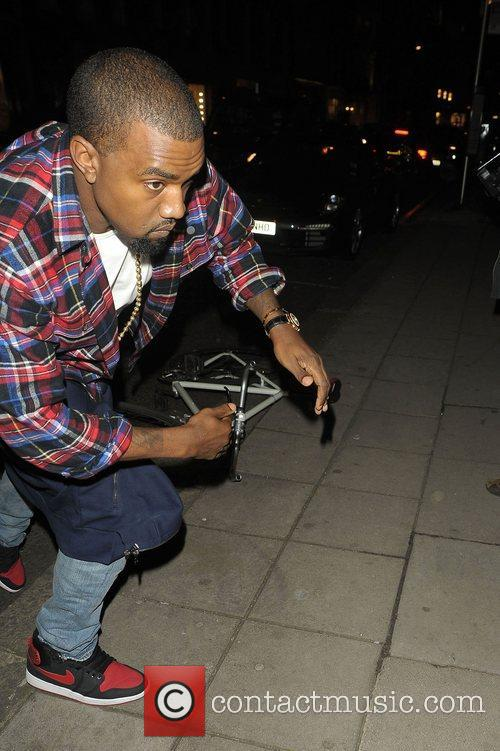 Kanye West trips over a kerb and quickly...