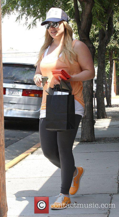 Hilary Duff wearing black leggings with orange trainers...