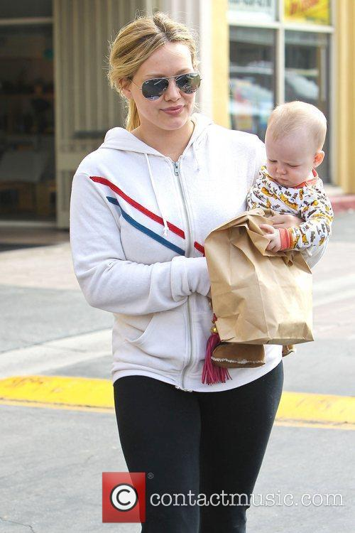 Hilary Duff carries her son Luca Cruz while...