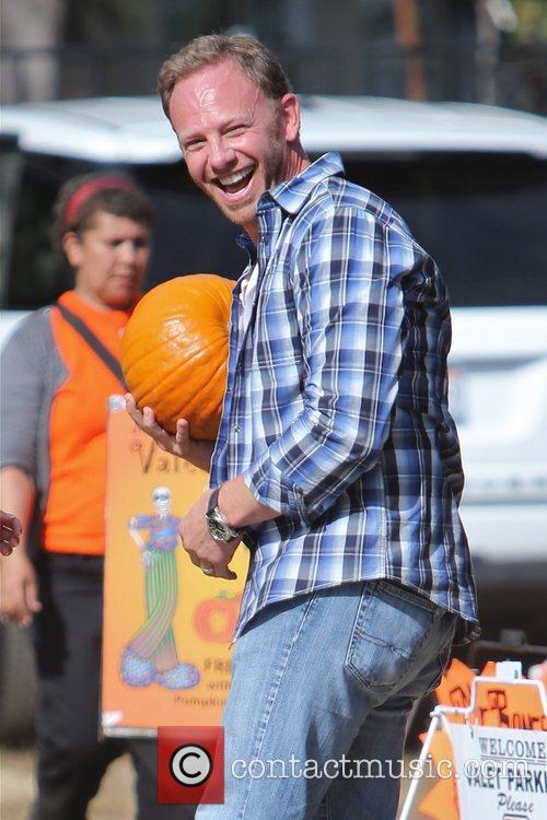 Ian Ziering pretends to put a pumpkin on...