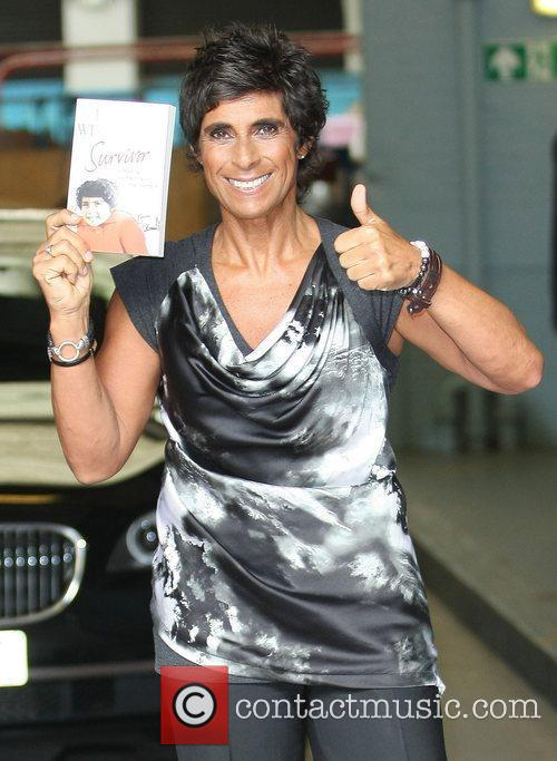 Fatima Whitbread holding a copy of her book...